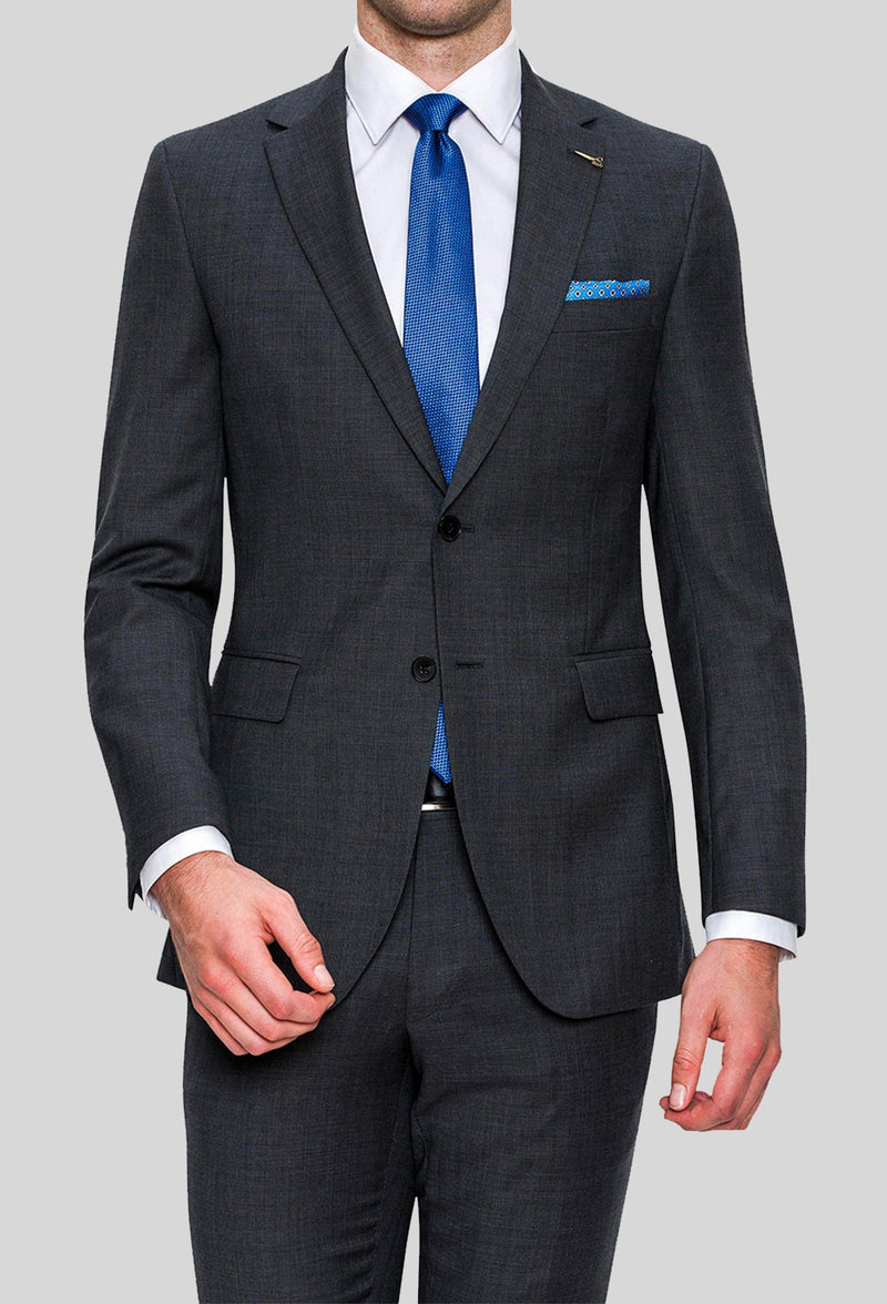 A model wears the Joe Black slim fit sergeant suit in charcoal pure wool FJD899 with a white shirt and a blue tie