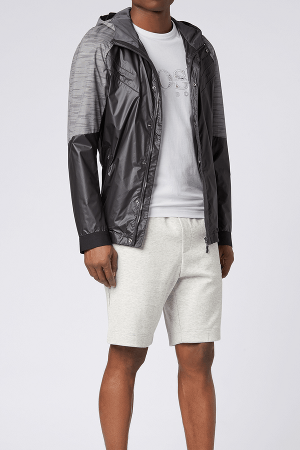 a model wears the mens hugo boss logo t-shirt in white 100% cotton with a grey windbreaker and knitted shorts