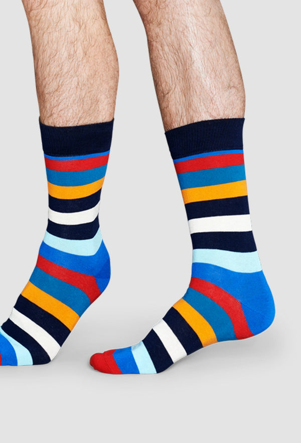 a model wears the Happy Socks stripe sock in blue orange red and white showing the socks sitting above the ankle
