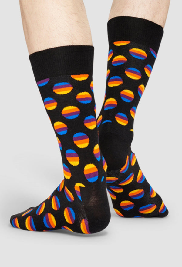 a model wears a pair of happy socks with sunrise dots in black combed cotton