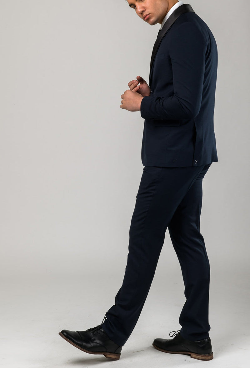 a model walks wearing the Aston slim fit laneport suit in navy A049301S