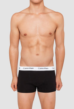a model wears the Calvin Klein black cotton stretch trunk with a white waistband and Calvin Klein logo in black writing