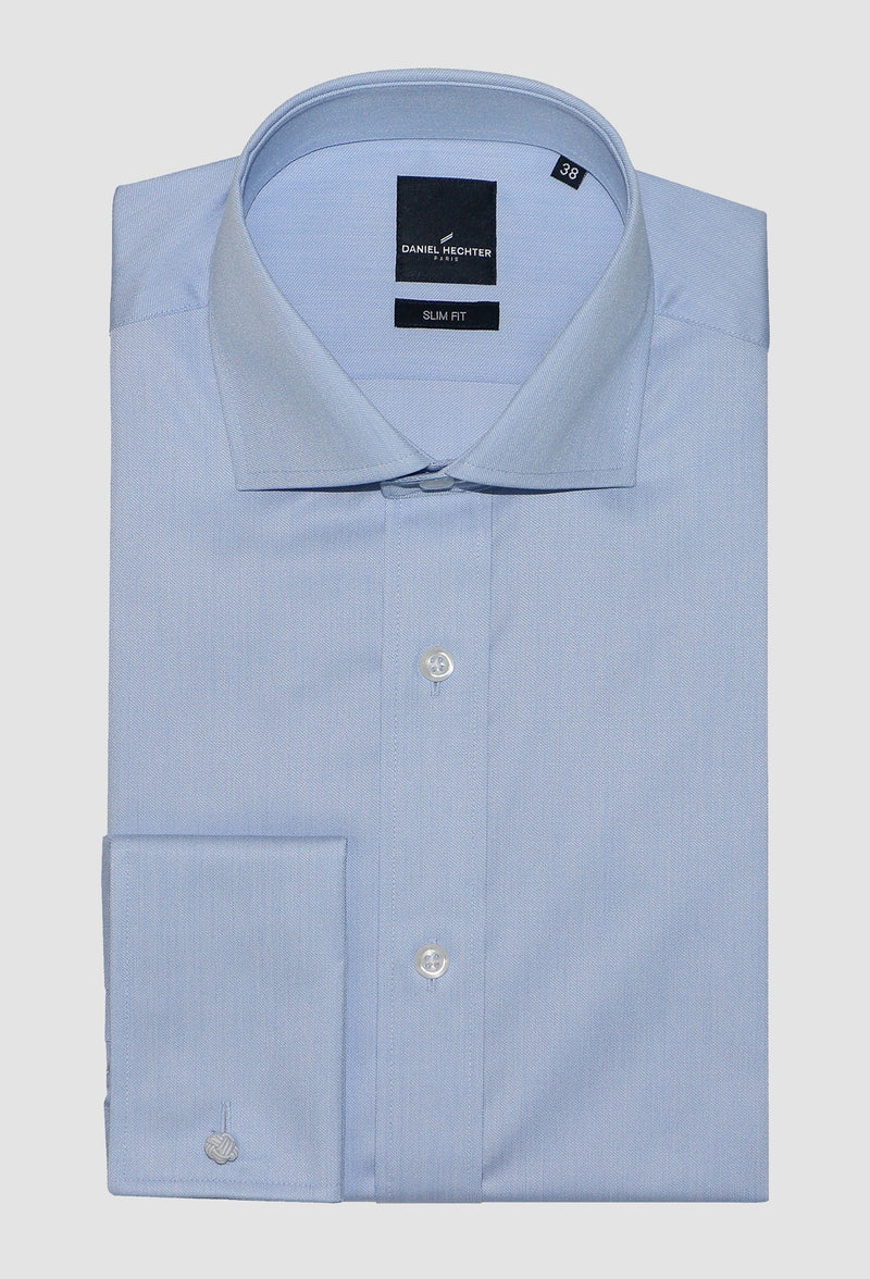 blue cotton business shirt by daniel hechter folded on a grey background showing the front button and french cuff detail