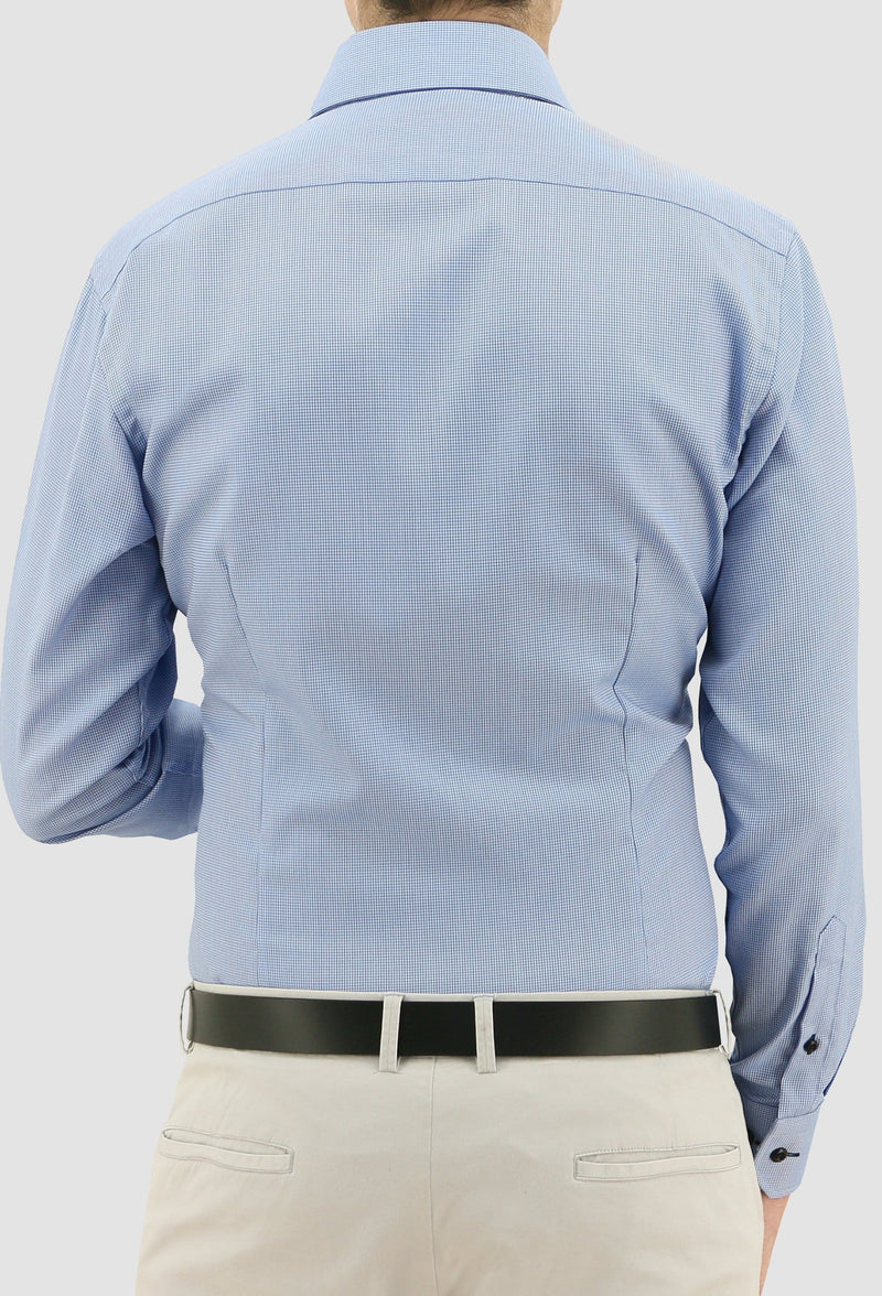 a model faces the back wearing the daniel hechter slim fit jacques business shirt in blue pure cotton styled with a chocolate brown belt and beige chino