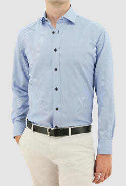 a model faces the front wearing the daniel hechter slim fit jacques mens business shirt in blue pure cotton styled with a chocolate brown belt and beige chino
