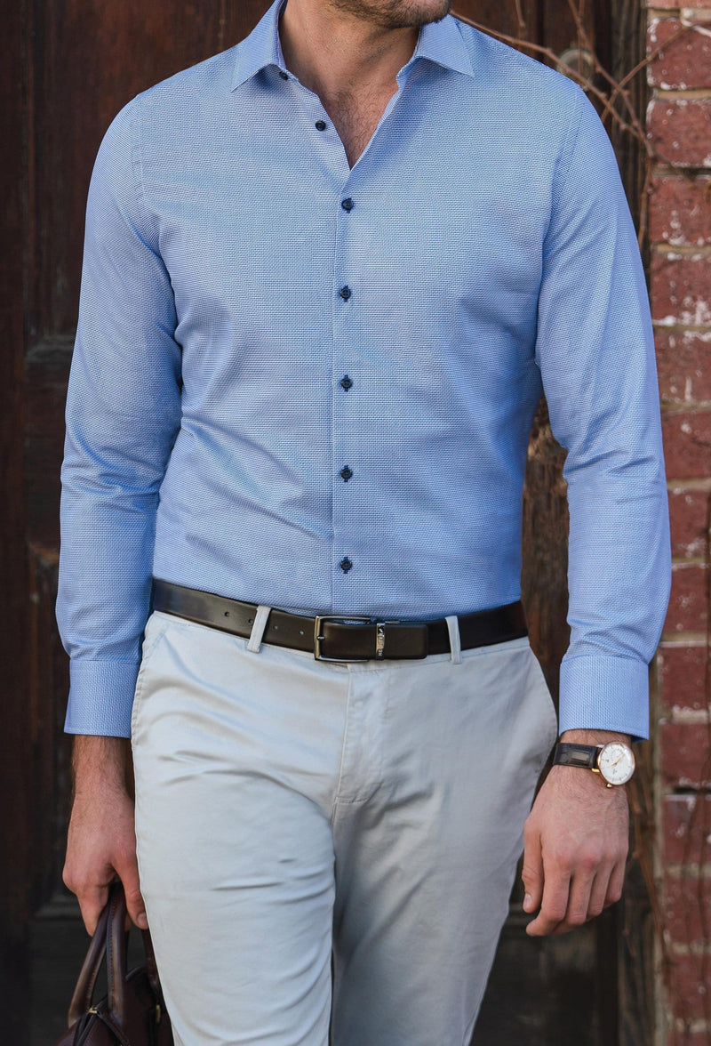 a model walks wearing the daniel hechter slim fit jacques mens business shirt in blue pure cotton styled with a chocolate brown belt and beige chino