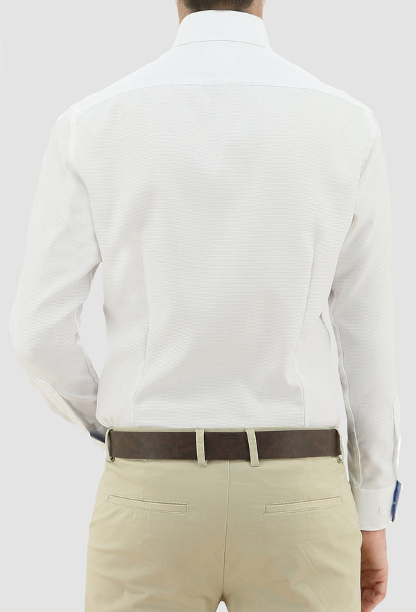 a model faces the back revealing the darted back on the daniel hechter slim fit jacques business shirt in white pure cotton styled with a chocolate brown belt and sand coloured trousers