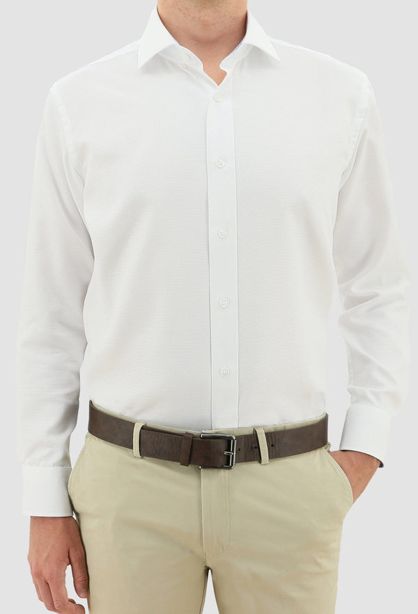 a model faces the front wearing the daniel hechter slim fit jacques mens business shirt in white pure cotton styled with a chocolate brown belt and sand coloured trousers