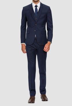 A front view of a model wearing the Gibson slim fit delirium suit in navy pure wool F3614 styled with a blue tie and white shirt