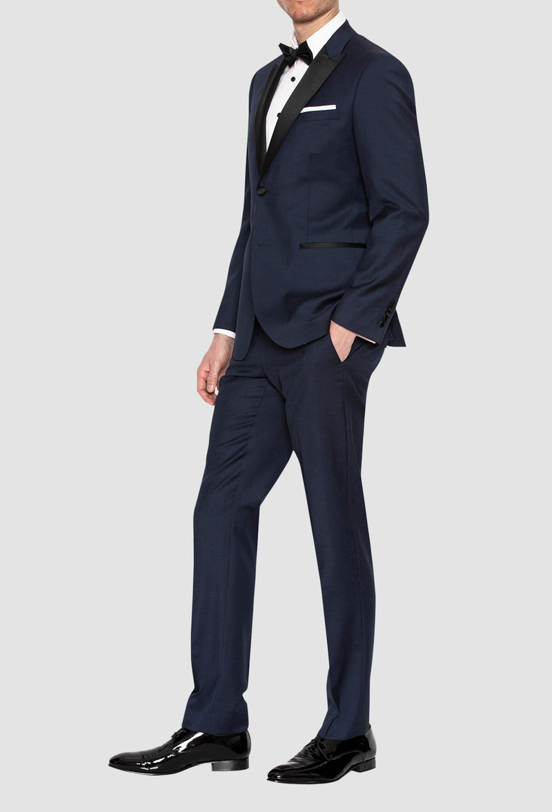 A side on view of a model wearing the Gibson slim fit quantum evening suit in navy pure wool F3614