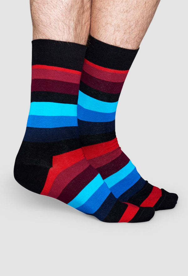 a model wears the happy socks stripe sock in black red and blue cotton SA01-068