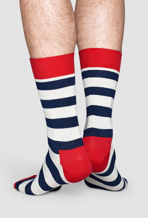 a model wears the Happy Socks stripe sock in navy red and white showing the higher cut of the sock