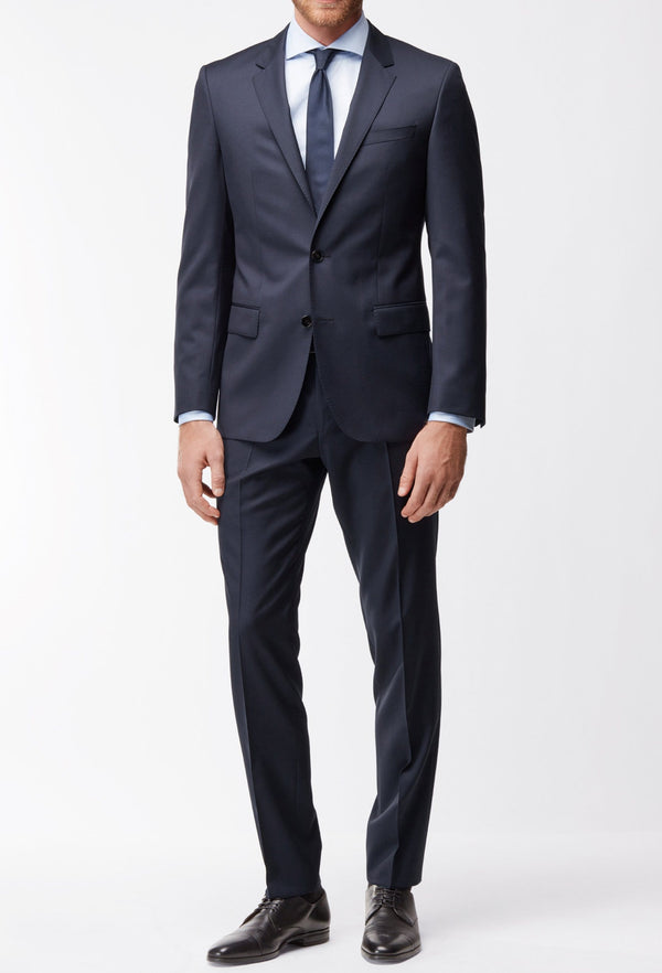 A full length frontal view of a man standing in the Hugo Boss classic fit johnstons suit in dark blue