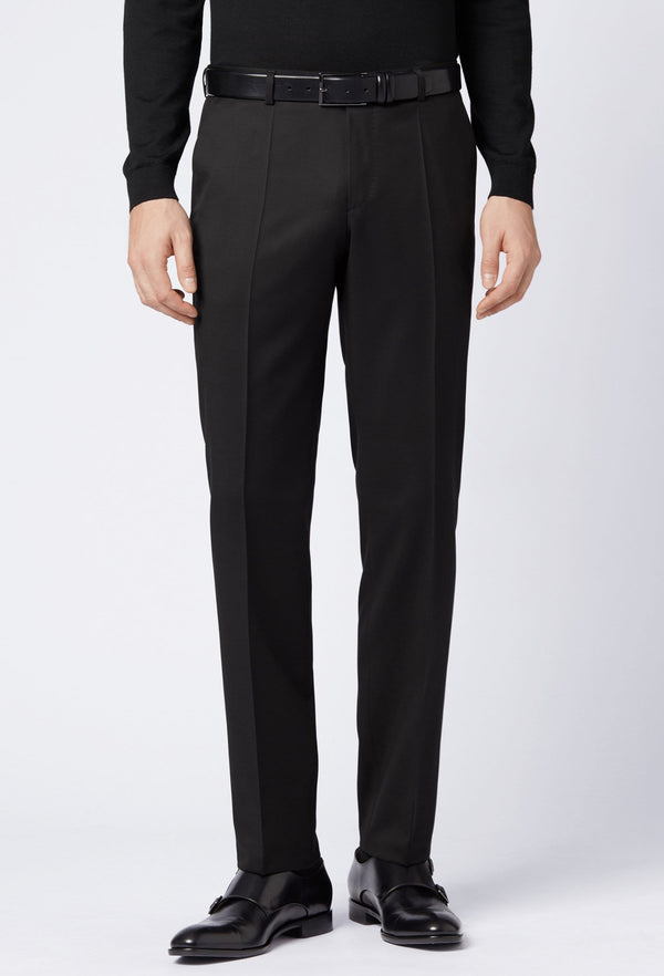 a front on view of a man standing in the Hugo boss lenon trouser in black, wearing black shoes and a black sweater