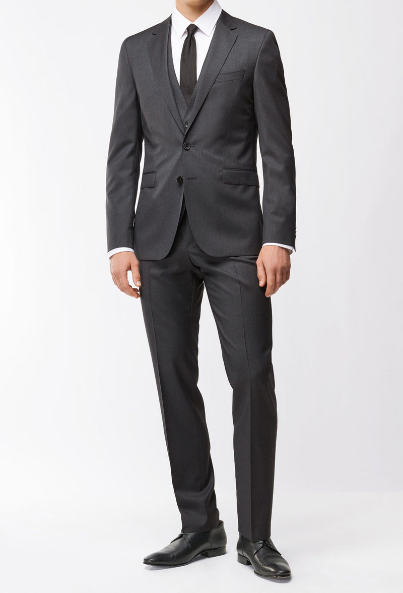 A model wears the Hugo Boss classic fit lenon trouser in dark grey pure wool HB50318825-021 styled as the trouser in the Hugo boss Johnston suit