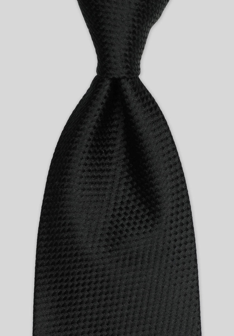 Joe black long stitch black tie tied with a Windsor knot on a grey background