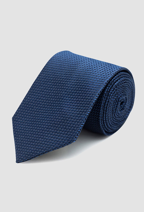 a close up of the Joe Black classic longstitch knot tie in navy PJAE000001 rolled up on a grey background