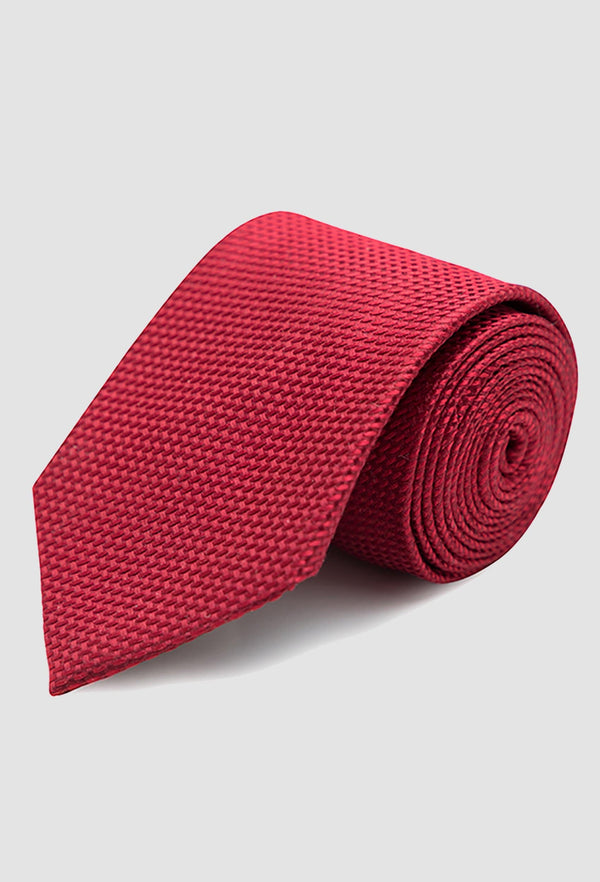 Joe Black classic longstitch knot tie in red PJAE000001 rolled up on a grey background