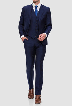 A model walking and wearing the Joe Black slim fit anchor suit in navy pure wool FJY100 styled with a white shirt and a blue tie