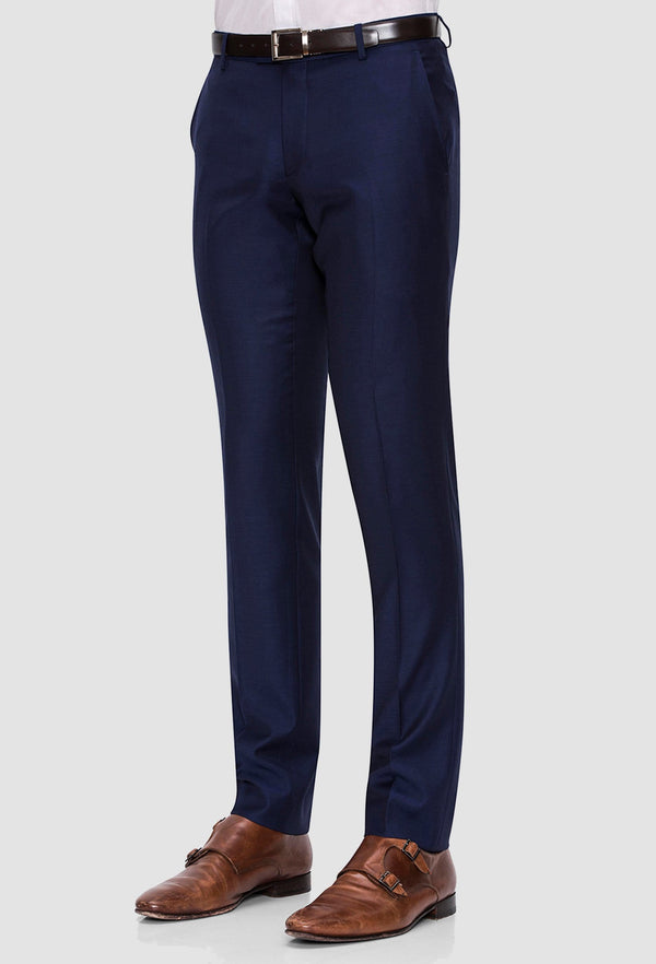 a side on view of the Joe Black slim fit razor trouser in navy pure wool styled with tan accessories