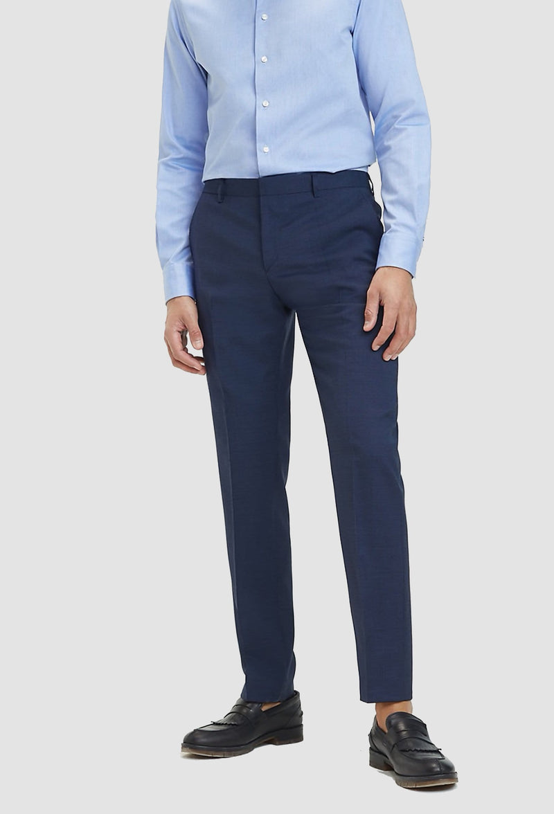 a model faces the front wearing the Tommy Hilfiger slim fit virgin wool trouser in navy blue styled with a light blue shirt
