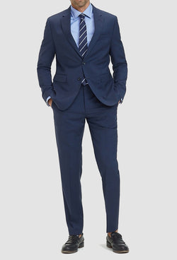 a model faces the front wearing the Tommy Hilfiger slim fit virgin wool suit in navy with a blue shirt and tie