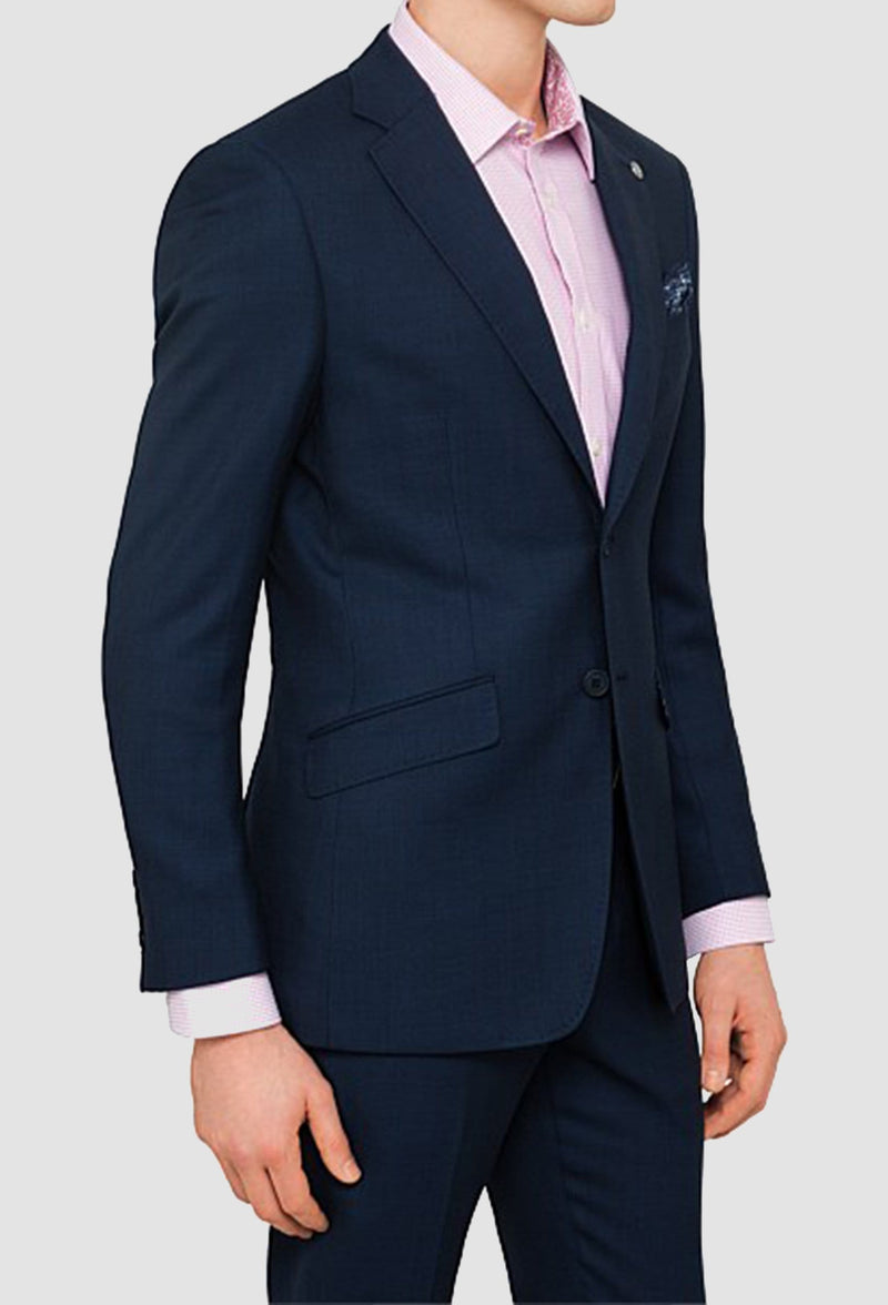 a side on view of the ted baker slim fit Birdseye suit in navy pure wool styled with a pink shirt on a grey background