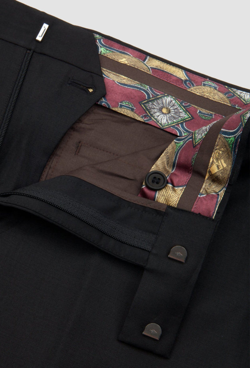 a close up view of the printed lining and hook eye fastener of the ted baker slim fit sovereign suit trouser in black wool