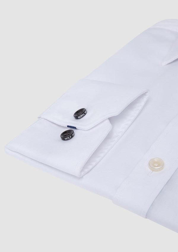 a close up of the romanov men's white business shirt with black branded buttons on the adjustable single cuff
