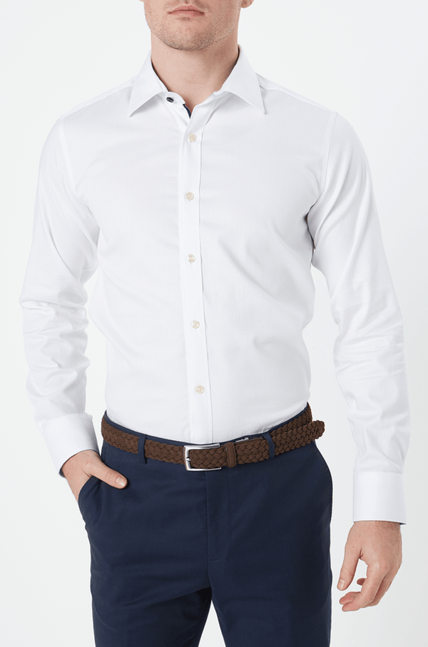 the front of the white herringbone mens business shirt tucked into a pair of navy trousers