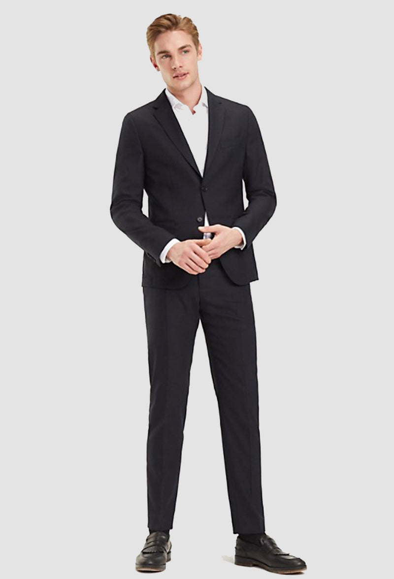 a model wears the Tommy Hilfiger slim fit virgin wool suit in black with a white shirt