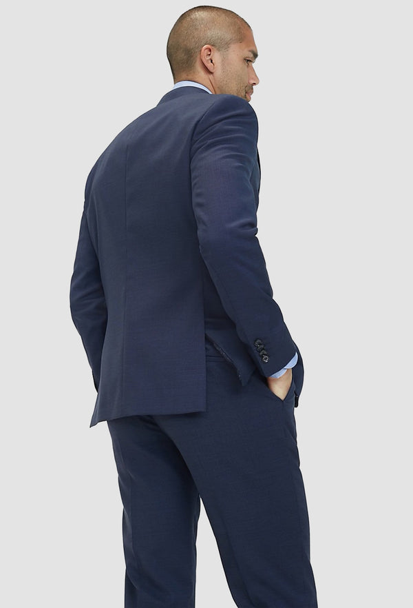 A model faces the back showing up the back details on the Tommy Hilfiger slim fit virgin wool blazer in navy blue