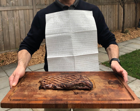 Man wearing a NEATsheet and holding a cutting board with grilled steak.