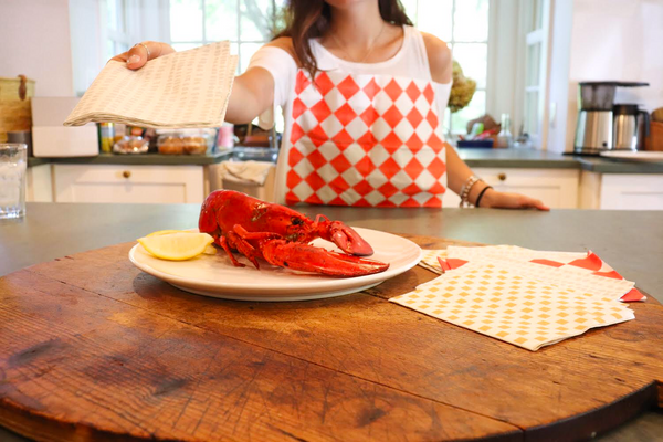 Woman eating lobster wearing a Red & White Diamond NEATsheet, a disposable clothing protector with easy-to-use adhesive tabs.