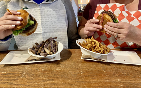 Two women eating burgers outside at a table wearing NEATsheets