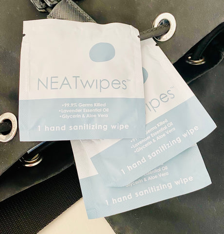 Individually wrapped NEATwipes on top of a shoulder bag.