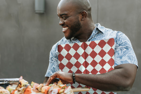 A man at a cookout wearing a Red & White Diamond NEATsheet, a disposable clothing protector with easy-to-use adhesive tabs.