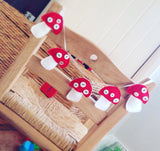 Five cute red and white toadstools hanging from white satin ribbon garland