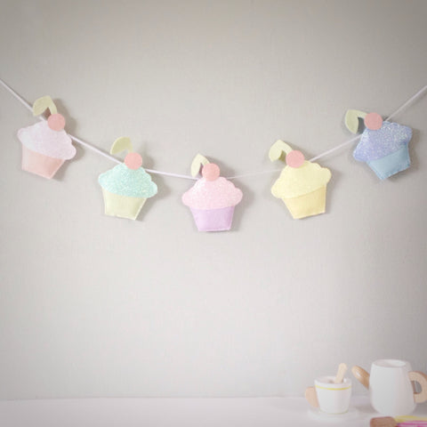 A cupcake garland made from felt and glitter, with three or five cupcakes