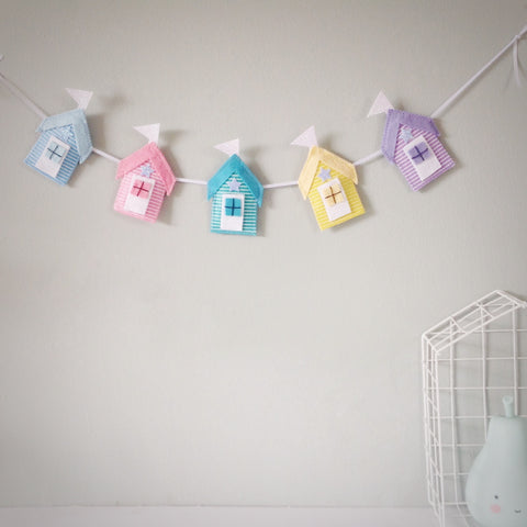 A beach hut garland, with five glitter and stripe felt beach huts