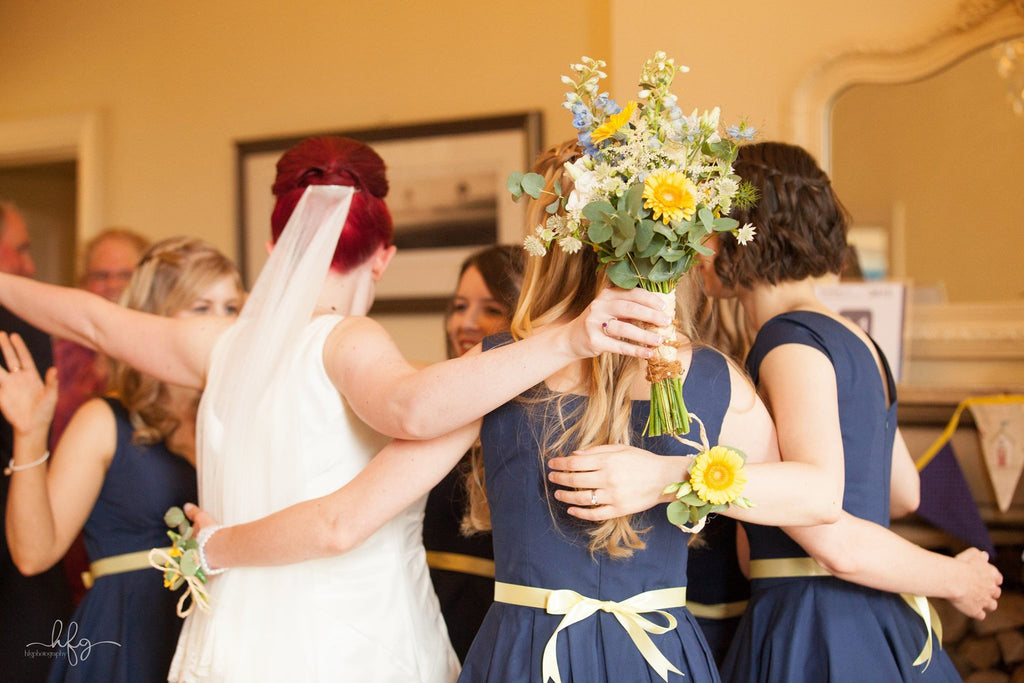 Bride and bridesmaid's with wedding bouquet and yellow Gerbera wrist corsages.