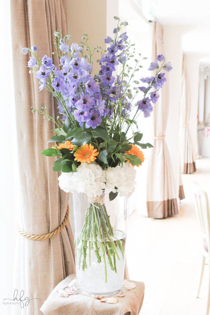 Venue decorations in glass vases with white Hydrangea, orange Gerbera and foliage.