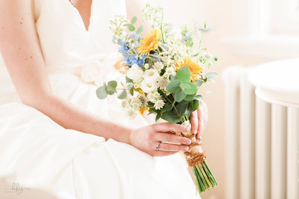 Bridal bouquet made with yellow Gerbera and flowers in shades of blue, white and green.