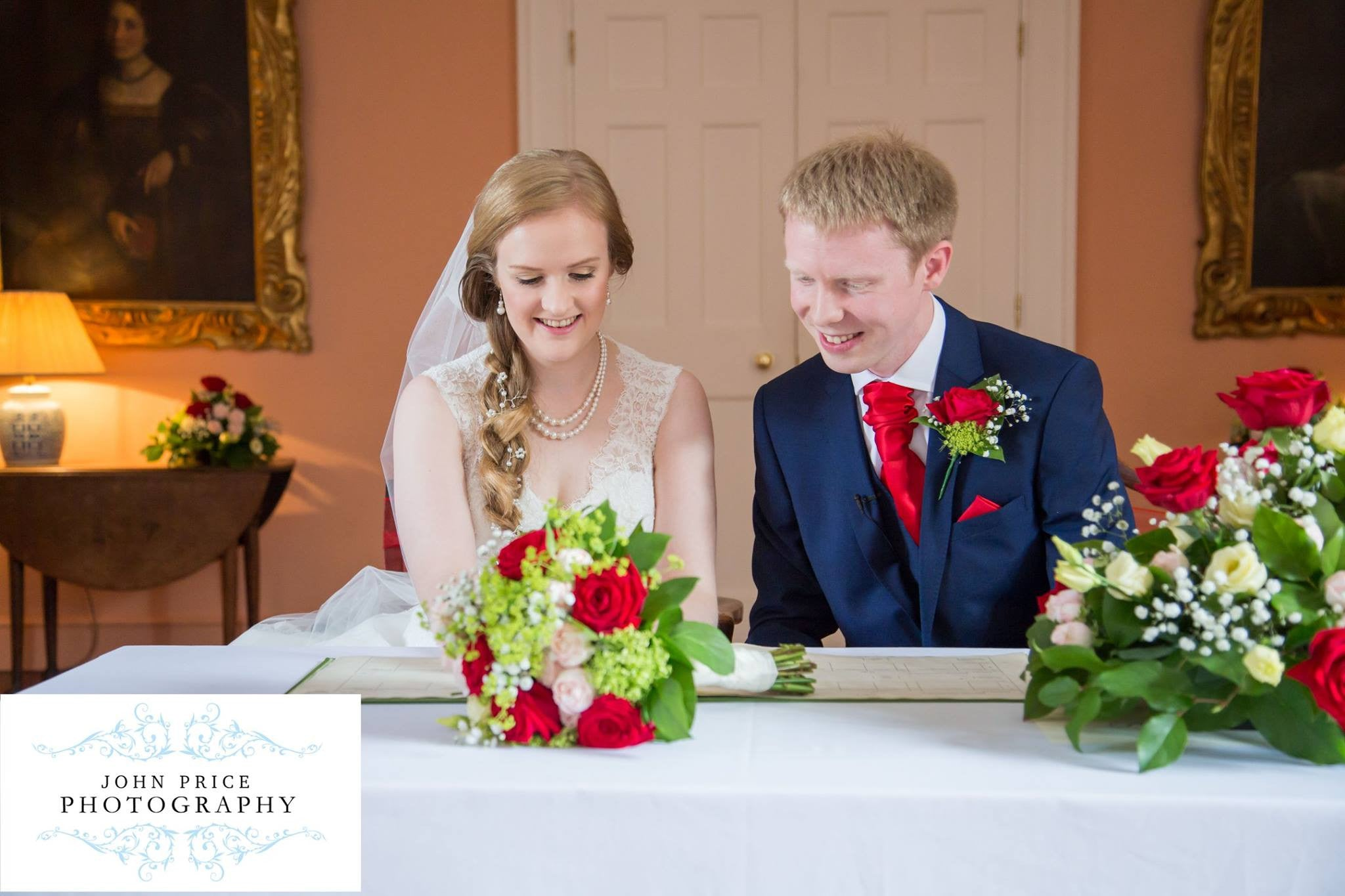 Bride and Groom signing wedding register with bridal flowers and buttonhole.