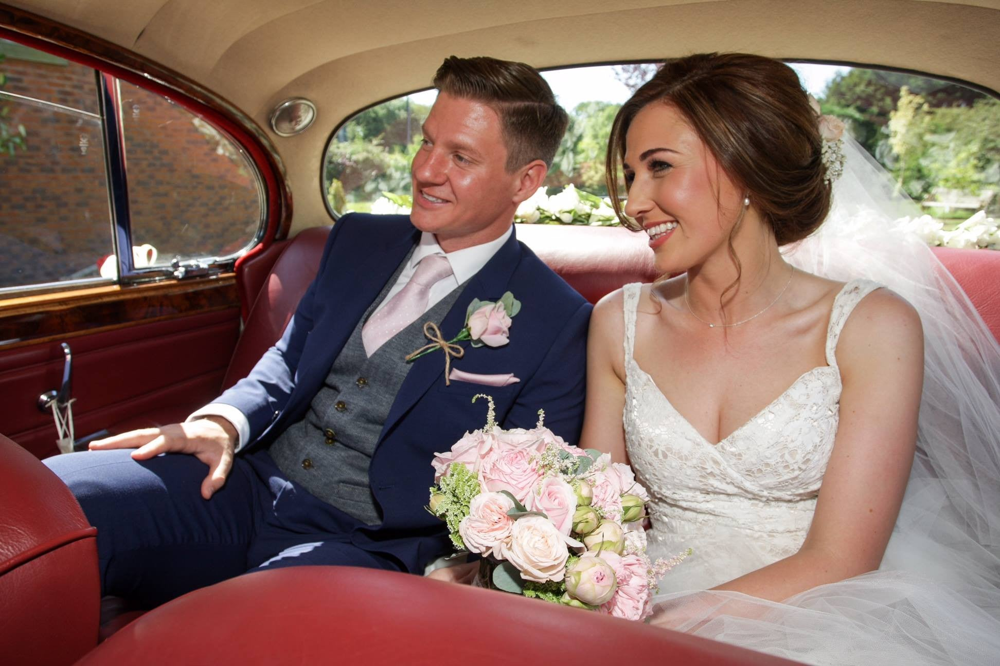 Bride and Groom in the wedding car with pink Rose bouquet and buttonhole.