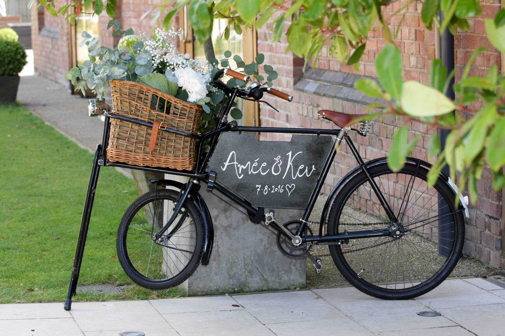 Vintage bike with wedding floral arrangement in shades of pink and cream in basket.