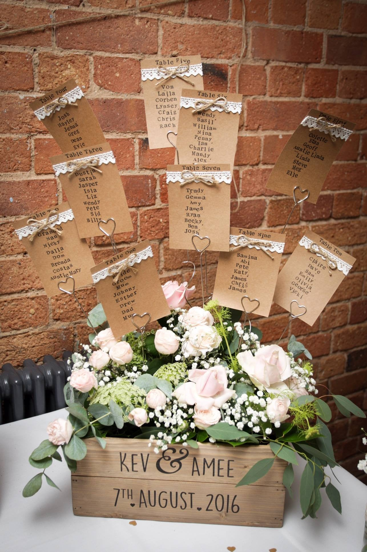 Wooden crate table seating arrangement with pink Roses, white Gypsophila and foliage.