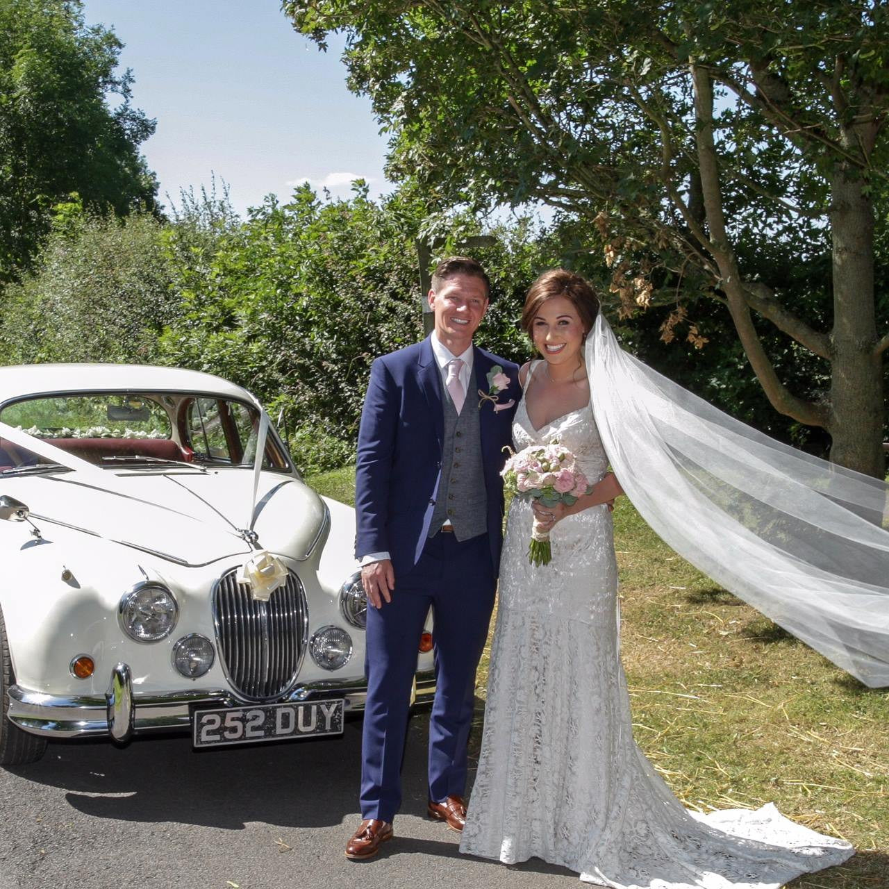 Bride and Groom with wedding car and wedding flowers.