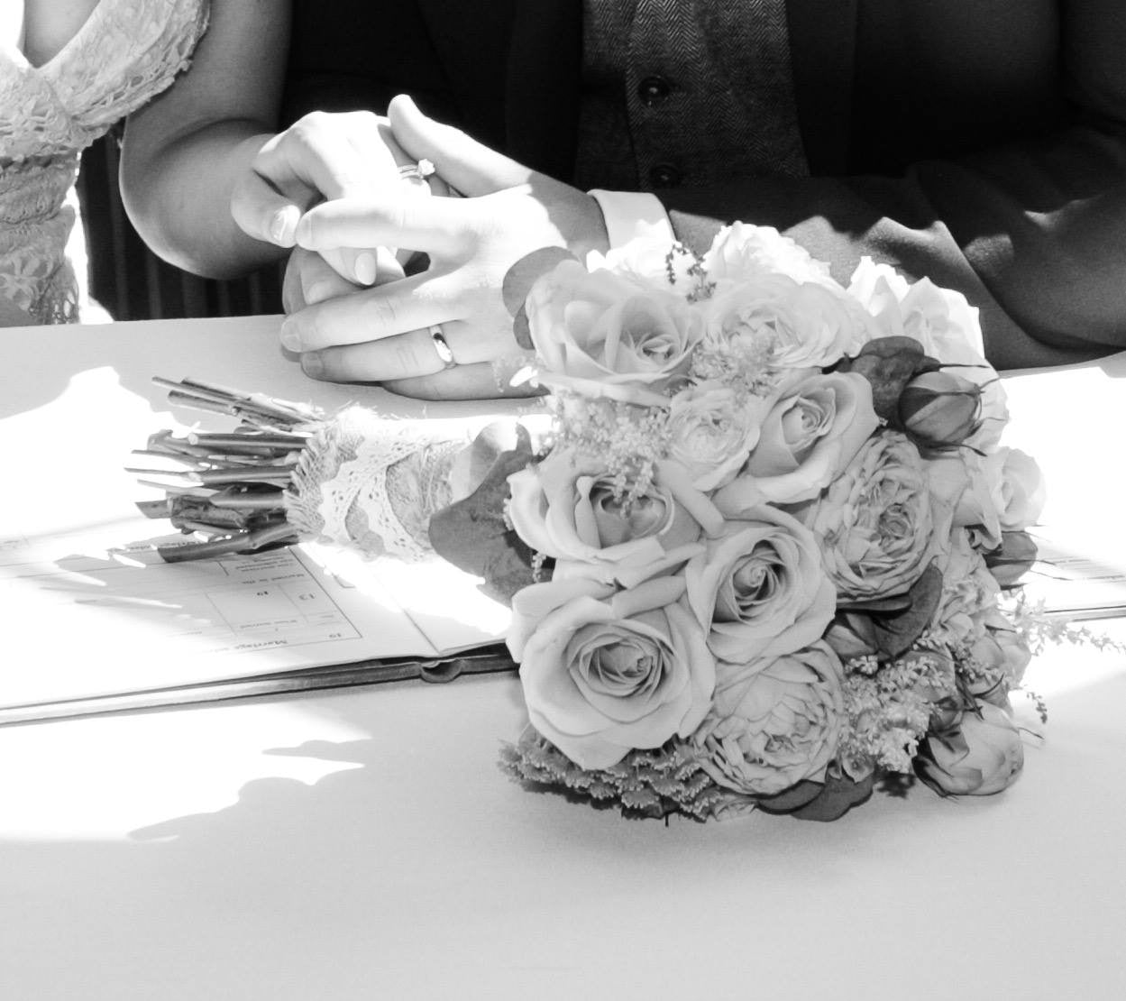 Wedding couple with wedding flowers signing the register.