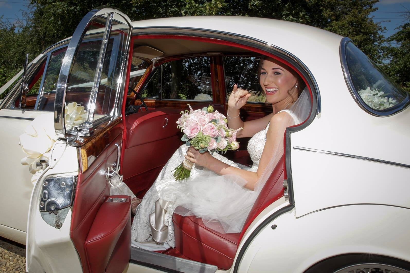 Bride with pink Rose bridal bouquet in the wedding car.